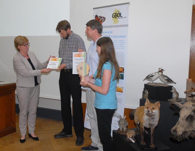 Dr. Christiane Paulus überreicht Urkunde, Plakette und einen symbolischen Baum an Björn Rulik, Dr. Matthias Geiger und Laura von der Mark (v.l.n.r.)