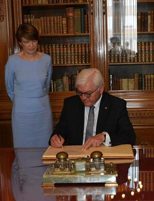 Der Bundespräsident trägt sich in das Gästebuch des Museums ein.