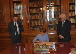 Frau Büdenbender trägt sich in das Gästebuch des Museums ein